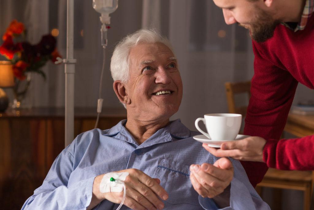 Male carer assisting incurable ill senior man