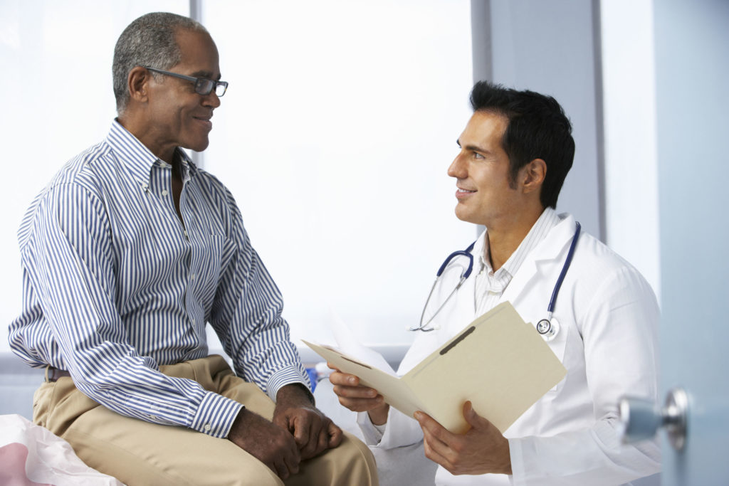 42256499 - doctor in surgery with male patient reading notes